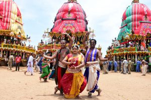 Dancers dance in front of chariots to show their devotion